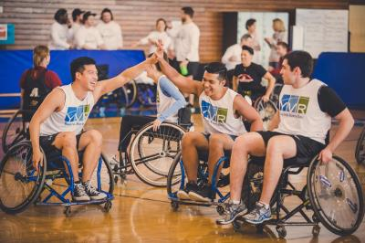 Two wheelchair basketball players high-fiving