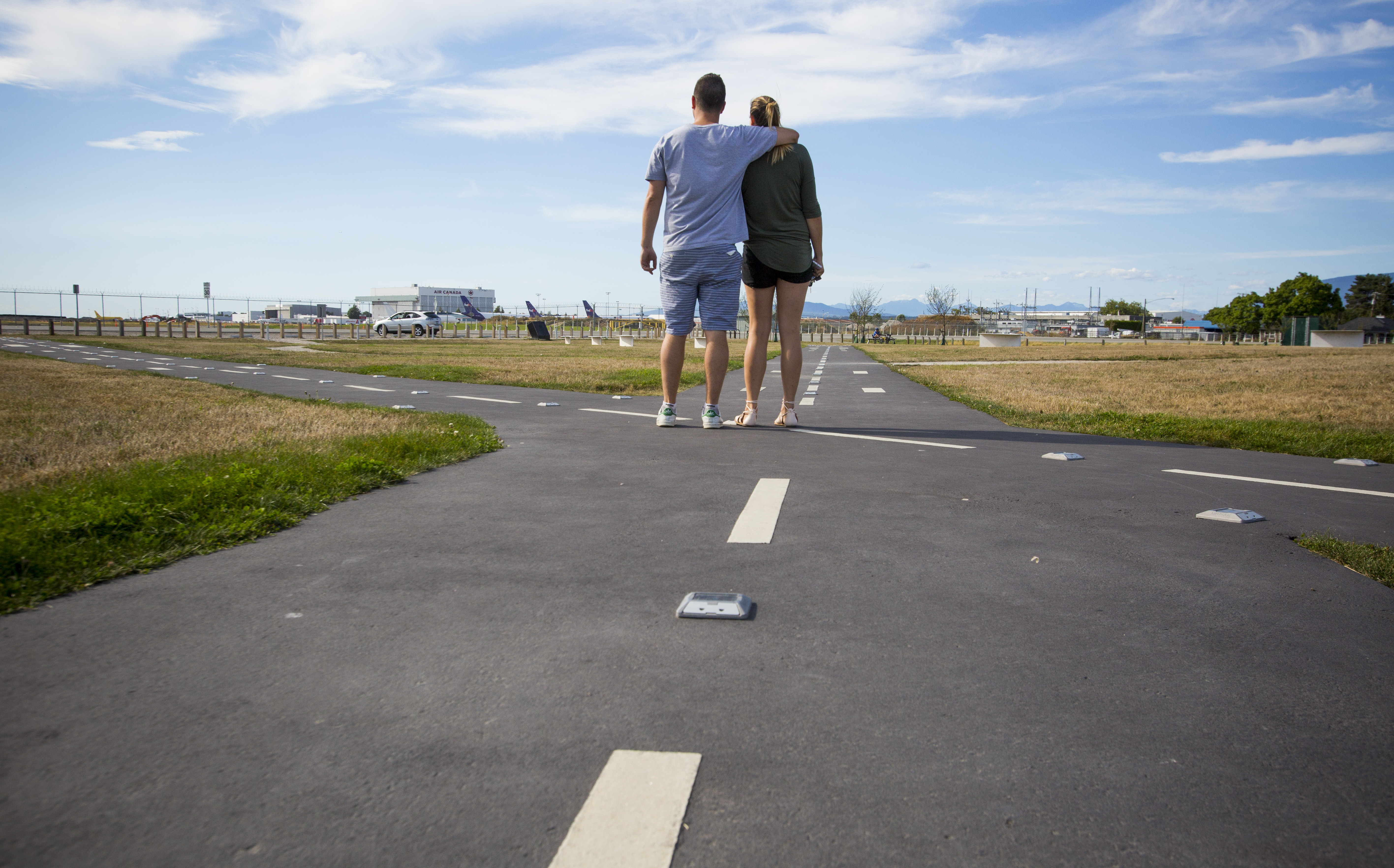 A couple at flight path park watching planes land.