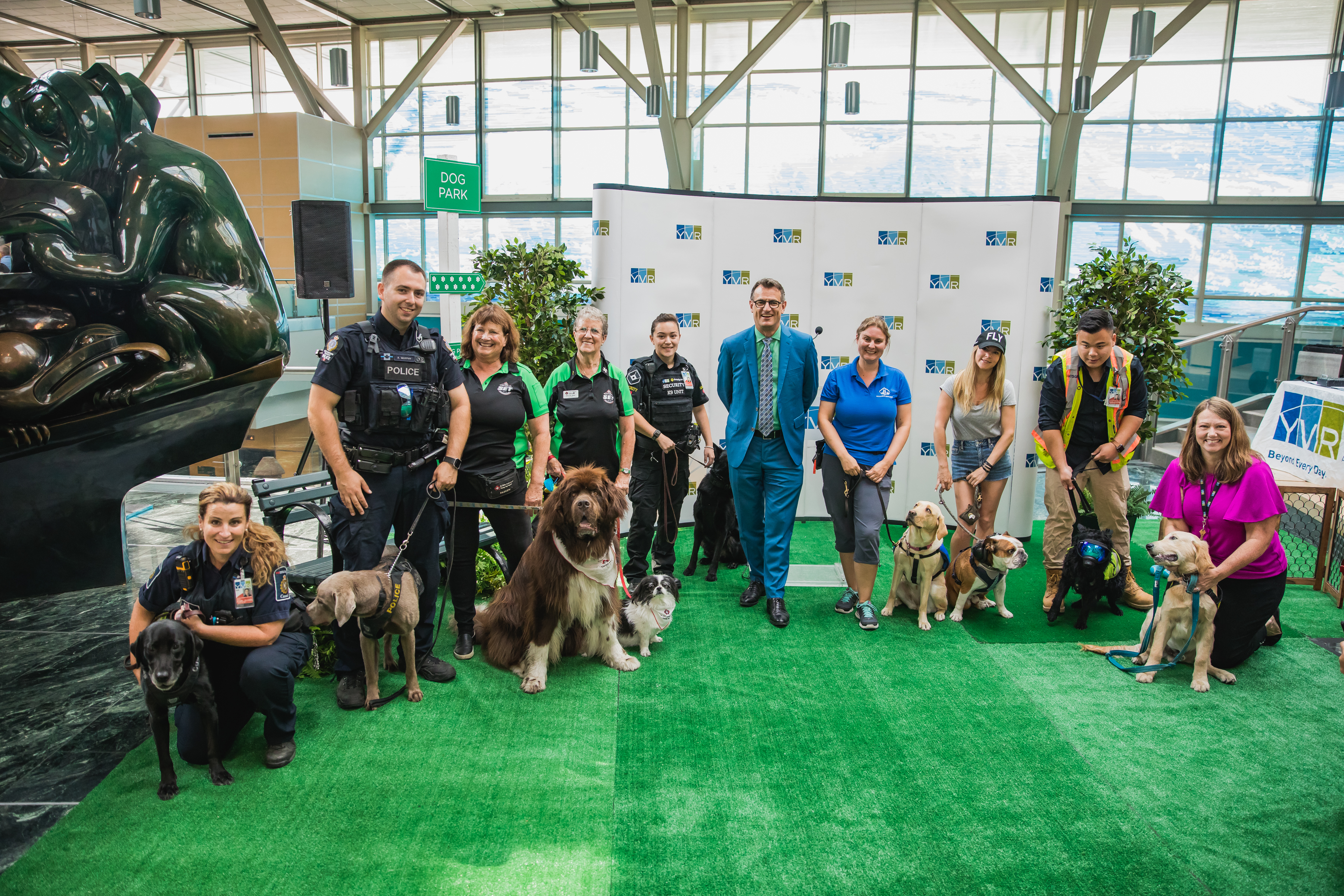 YVR celebrated the first ever Dog Days of Summer event at the airport. From left to right are representatives from Canada Border Services Agency (CBSA); Transit Police; St. John Ambulance; Securiguard; Reg Krake, Director, Customer Care, Vancouver Airport Authority; BC & Alberta Guide Dogs; Mister Bentley; YVR's Wildlife Team in partnership with Avisure and Pacific Assistance Dogs Society (PADS).