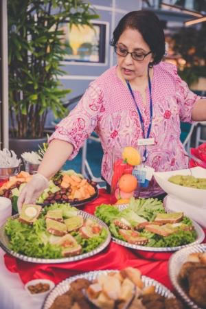 Narinder plating food at a special gate event