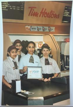 Narinder and three other Tim Horton's employees at the grand opening of YVR's first Tim Hortons location