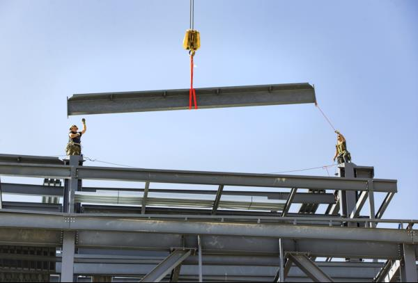 The final steel beam hovers above Pier D before it's final placement