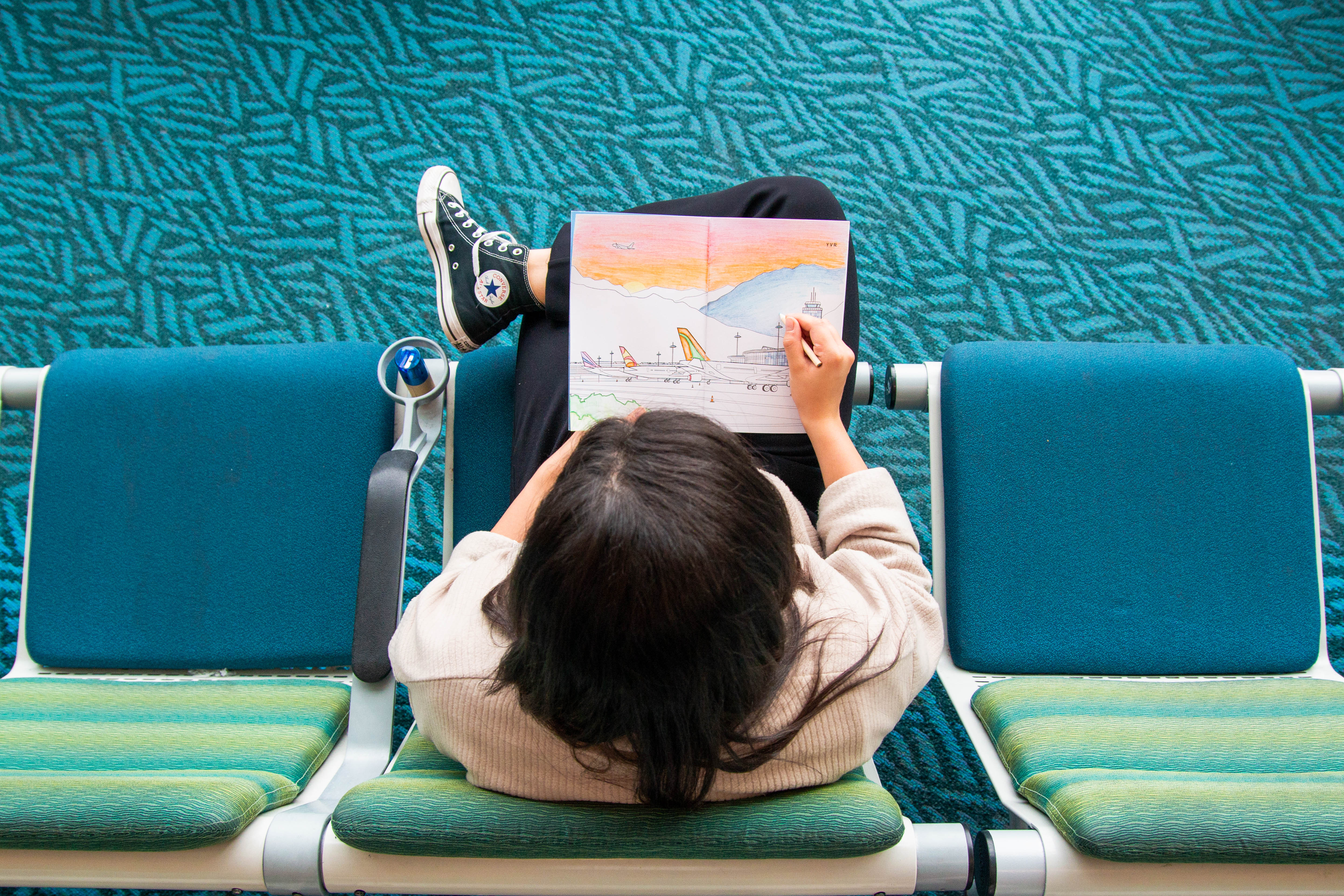 A passenger using the Fly Calm colouring book at the airport.