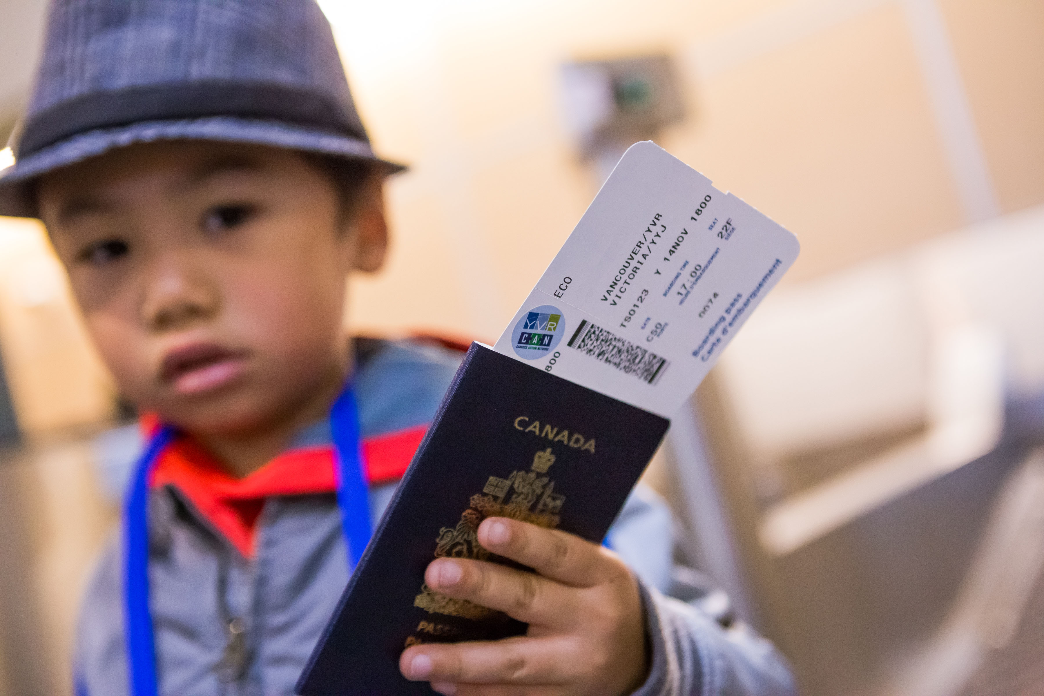 Little boy holding passport with boarding pass with an autism access sticker